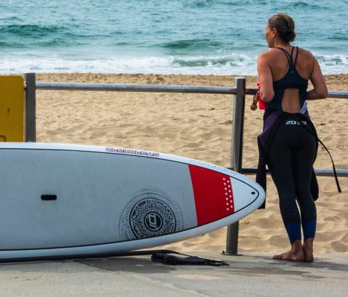 image d'une femme en combinaison de surf regarde l'horizon