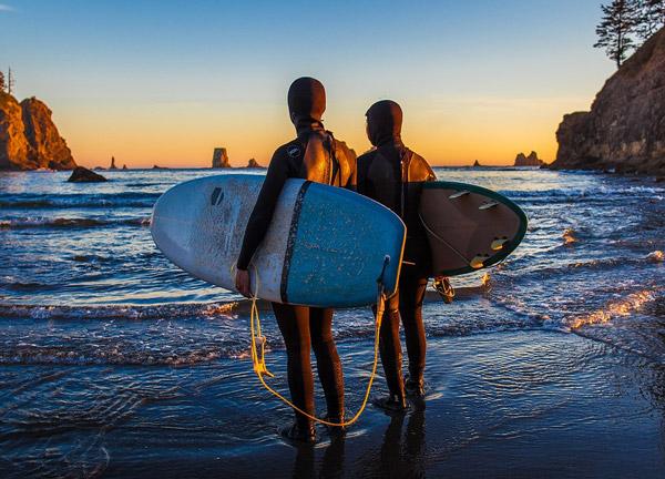 image de deux surfeurs sur une plage qui portent une combinaison intégrale
