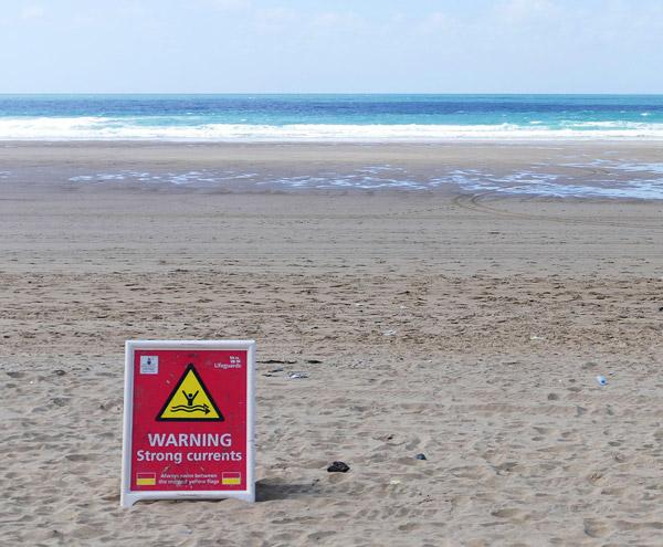 image d'une plage et d'un panneau qui indique de fort courent
