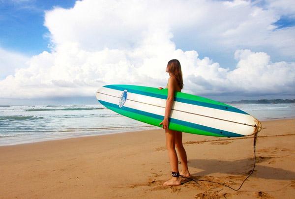 image d'une femme sur la plage qui tient sa planche de surf