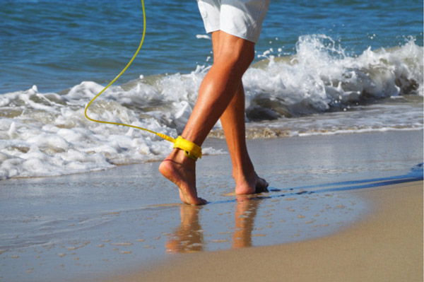 Image de la cheville d'un surfeur à laquelle est attaché le leash de sa planche