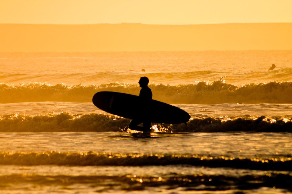 image d'un homme qui va nettoyer sa planche dans l'eau de mer