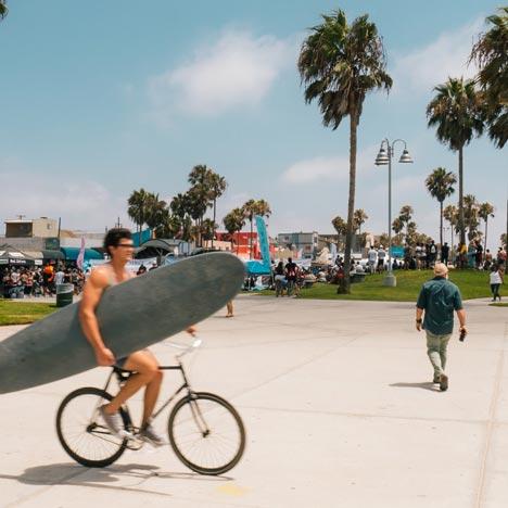 image d'un surfeur sur son vélo qui tient sa planche à la main