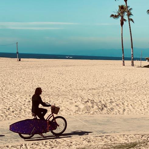 image d'un surfeur sur son vélo qui transporte une planche de surf grâce à un rack