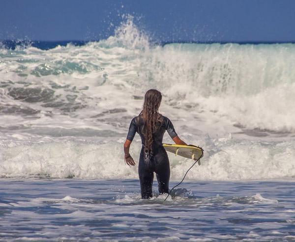 image d'une surfeuse dans l'eau s'appretant à nettoyer sa planche