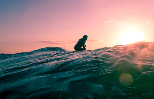image d'un surfeur qui regarde le couché du soleil sur sa planche : les bienfaits du surf sur le mental
