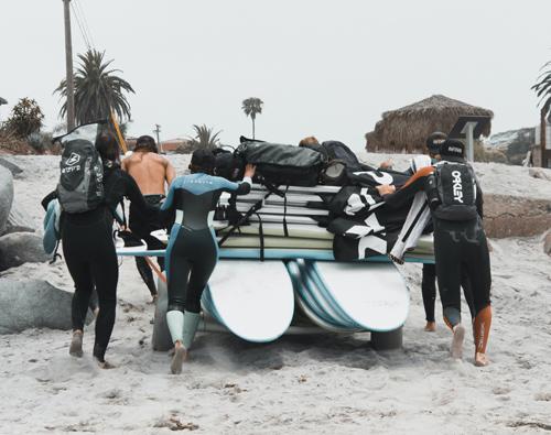 image d'un groupe de surfeur qui pousse une remorque avec une vingtaine de planche de planche posées dessus